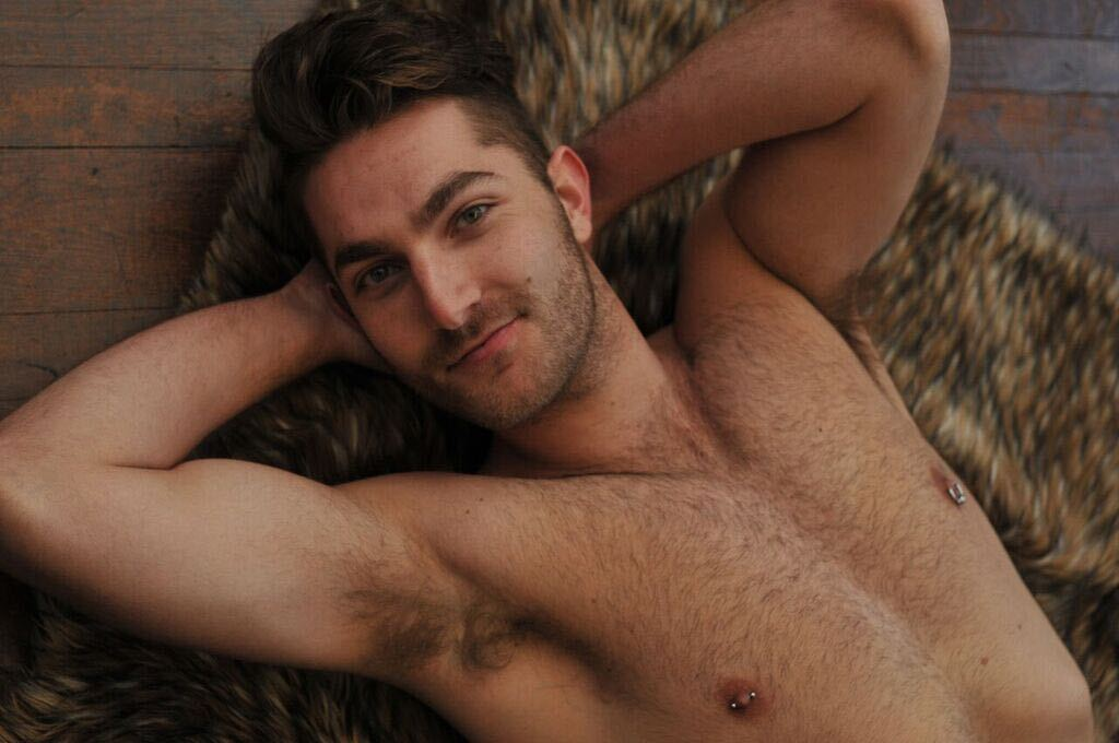 Zachary Zane poses topless with his muscular arms behind his head, his nipple piercings glistening.