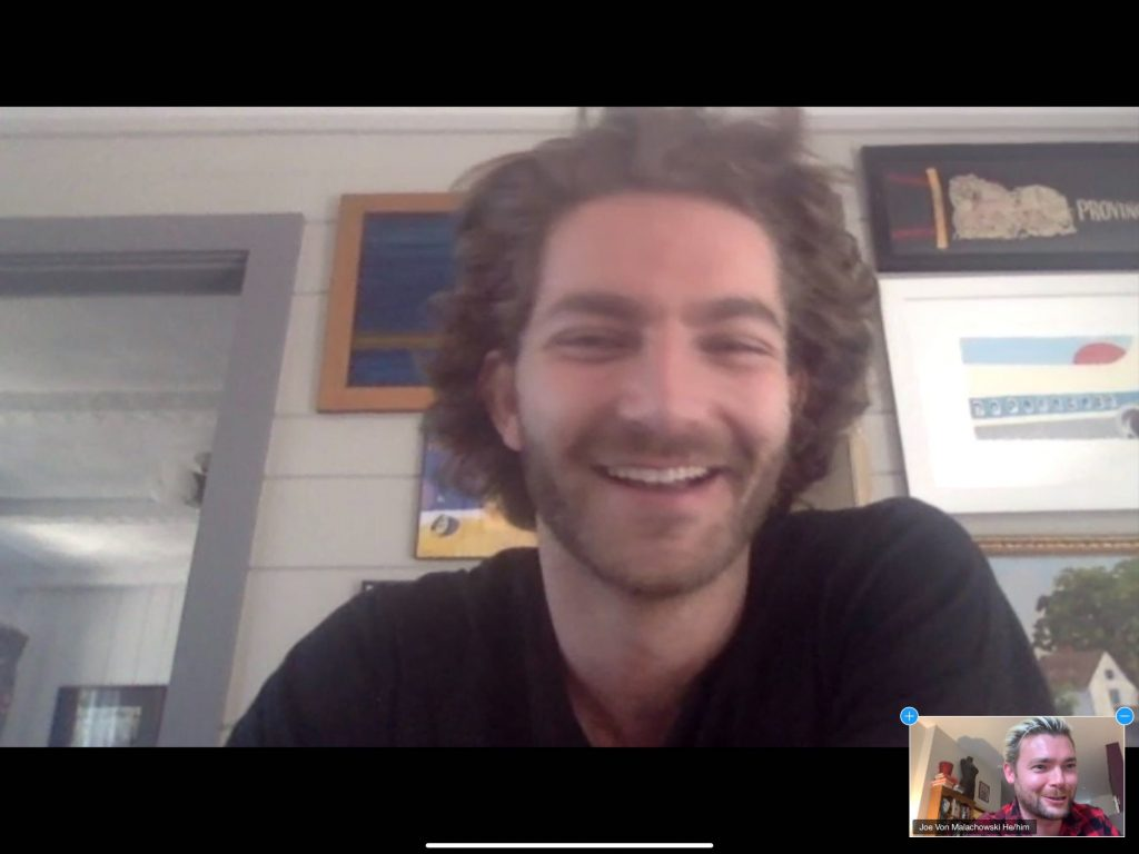 Zachary Zane smiles on a webcam screenshot of the interview. An image in the corner of the screen shows interviewer Joe von Malachowski blushing.