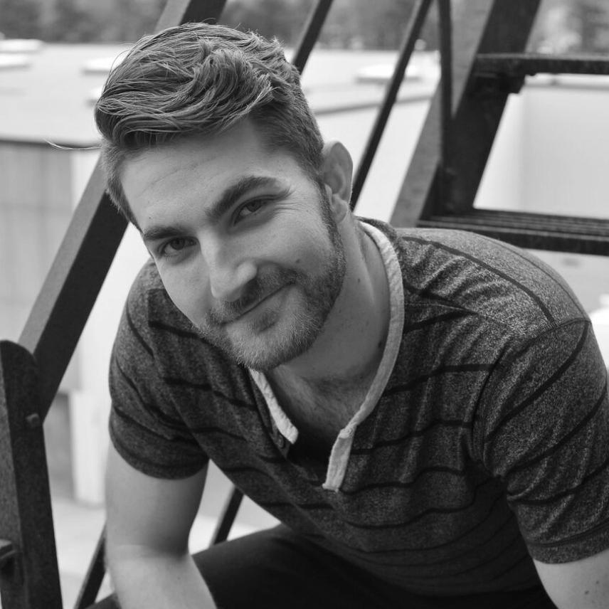 Zachary Zane poses on a fire escape, smiling.