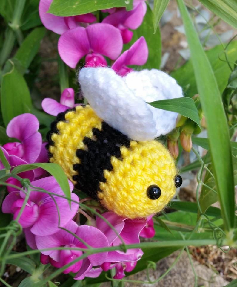A close-up of a yellow and black crocheted bee on a bed of pink flowers. It has a round fabric body,, two black dots for eyes, and white wings on top.