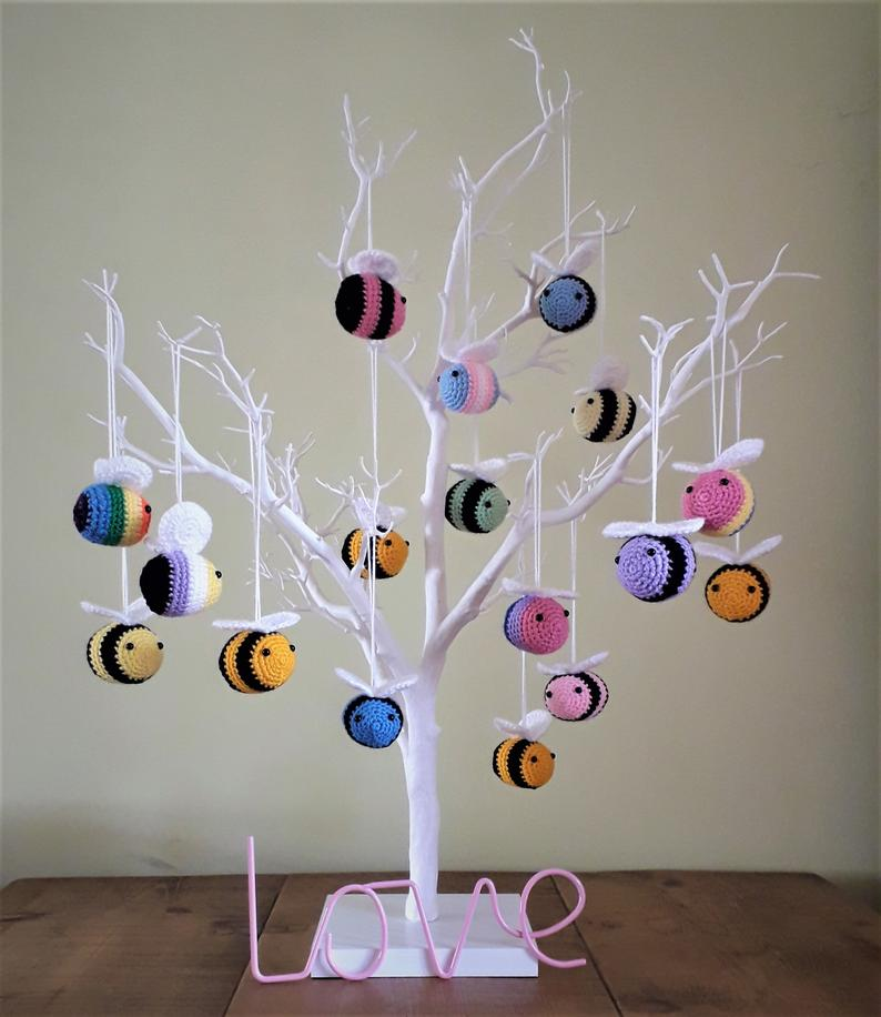 On a white bare tree ornament, lots of little crochet bees are hanging from a long white string like an ornament. They look adorable, and are in striped in lots of different colours including rainbow, pan, trans and bi flag colours.