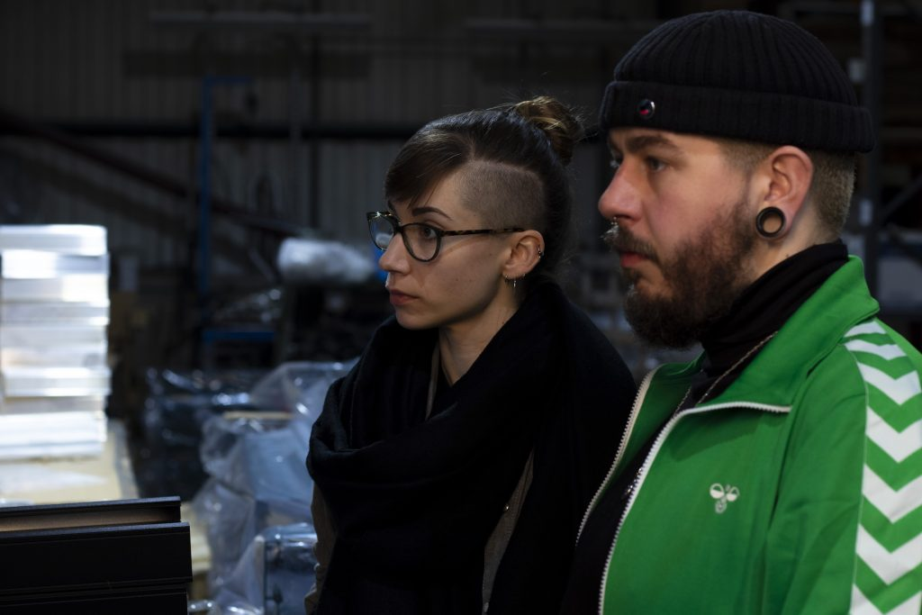 Behind the scenes photo of Chris and Lucie in the factory. Both are positioned to the right of the frame looking to the left. Chris wears a beanie hat and green patterned jacket. Lucie wears glasses and a black coat.