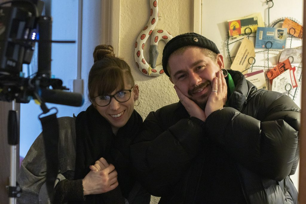 Behind the scenes shot of Lucie and Chris. Lucie is on the left of the photo holding her hands across her body. Her hair is up in a bun, she has a fringe and glasses. She is smiling. Chris has a beanie and puffer coat on. His hands cup his either side of his face he is smiling too.