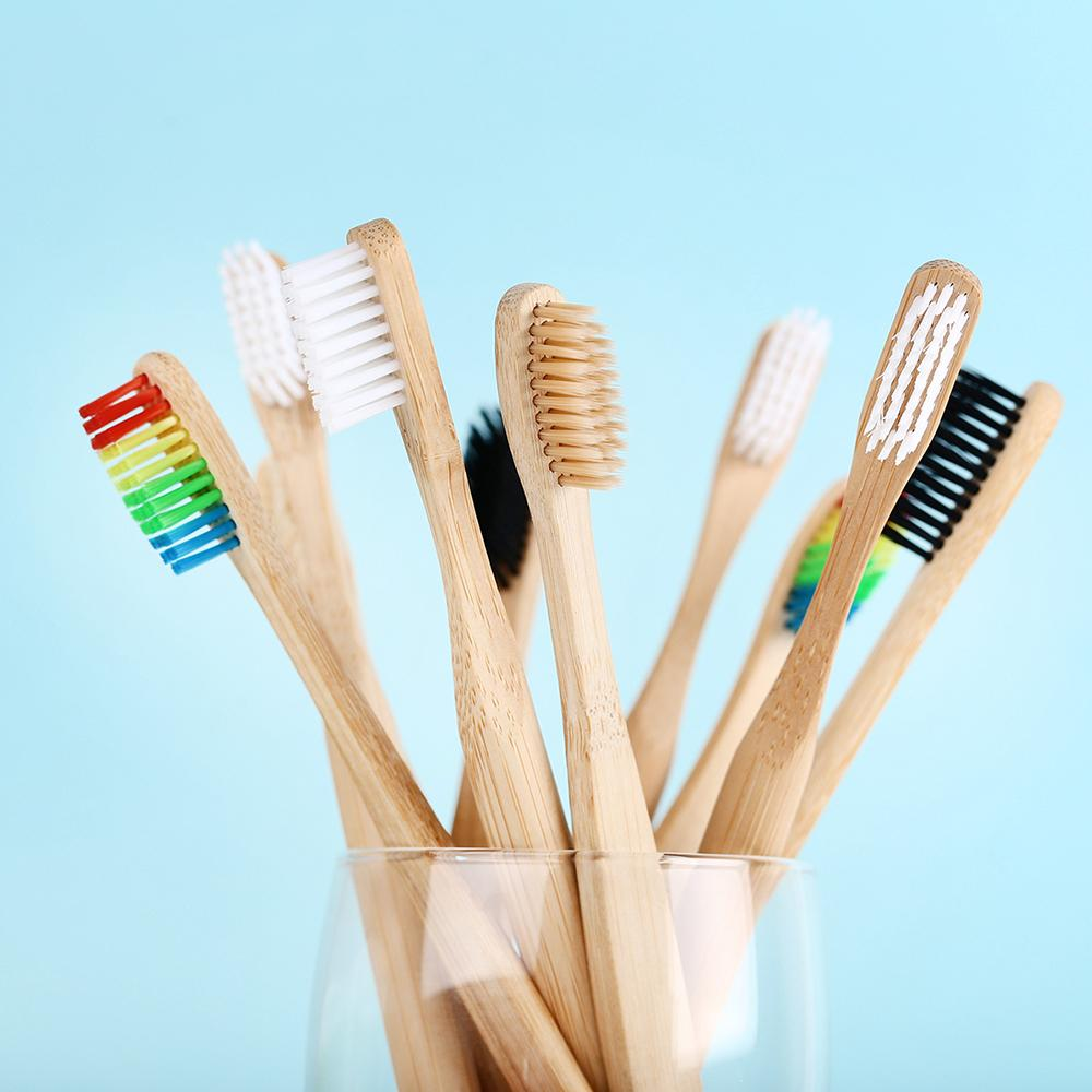 On a sky blue background, a pot of 9 bamboo toothbrushes are jutting from a glass at random angles. Their bristles are rainbow, white, black or hemp-coloured.