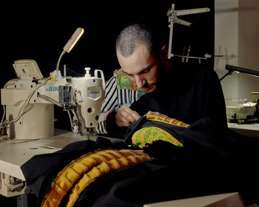 Zero Waste Daniel is bent over his sewing station, working on a colourful piece of black and yellow fabric with his hands.