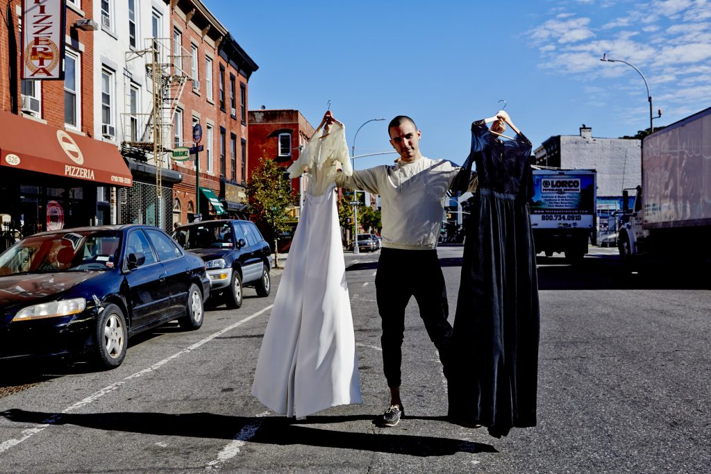 Daniel Silverstein holding up two zero-waste jumpsuits - one white & cream - one navy blue - in the street outside a pizzeria