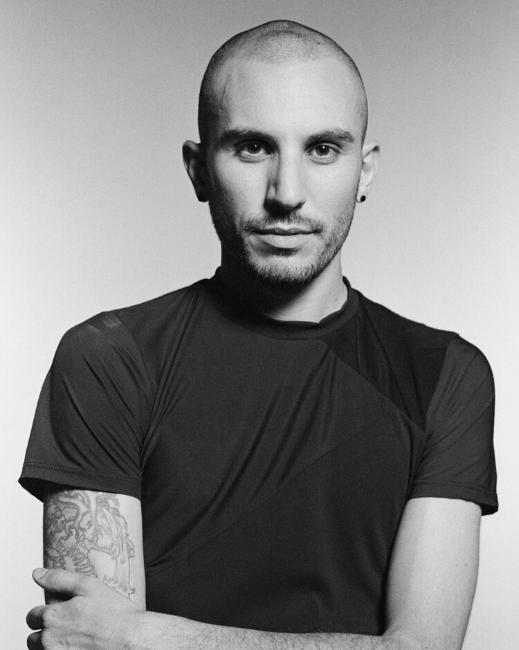 Black and white headshot of Zero Waste Daniel in a black tee. His arms are folded across his chest, his right arm shows off half of a cool sleeve tattoo, and his head is shaved.
