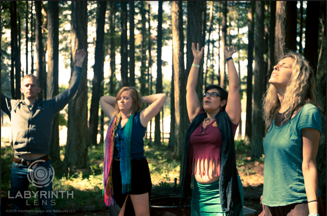 In the middle of a forest, shading them mostly from the sun, four people are communing with nature. The 1st and 3rd in the group have their hands held high as if praising the sky, the 2nd has their hands behind their head with their eyes closed in contemplation, and the final person has their arms by their side, eyes closed and head up to the sun.