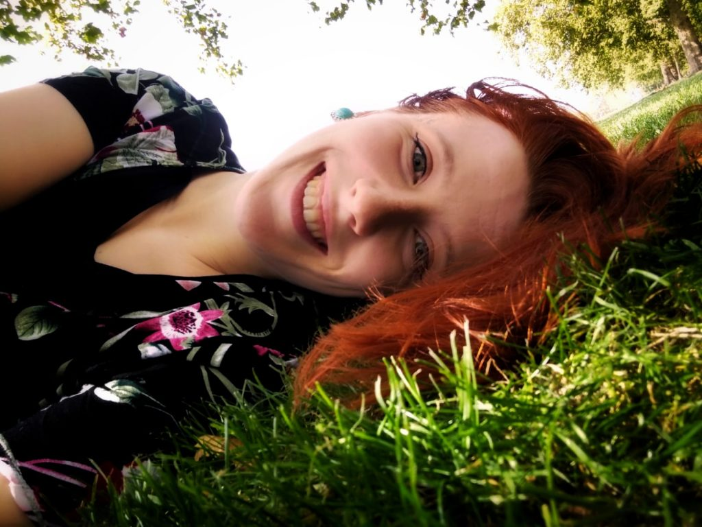 Lying on the bright green grass with leaves on trees and a bright white sky in the background, Maddie, a pale Caucasian woman, is lying side-on the the camera and smiling. In the shade, her newly dyed bright ginger hair is spilling down onto the grass, falling down to her shoulders. She is wearing a black floral patterned summer dress.