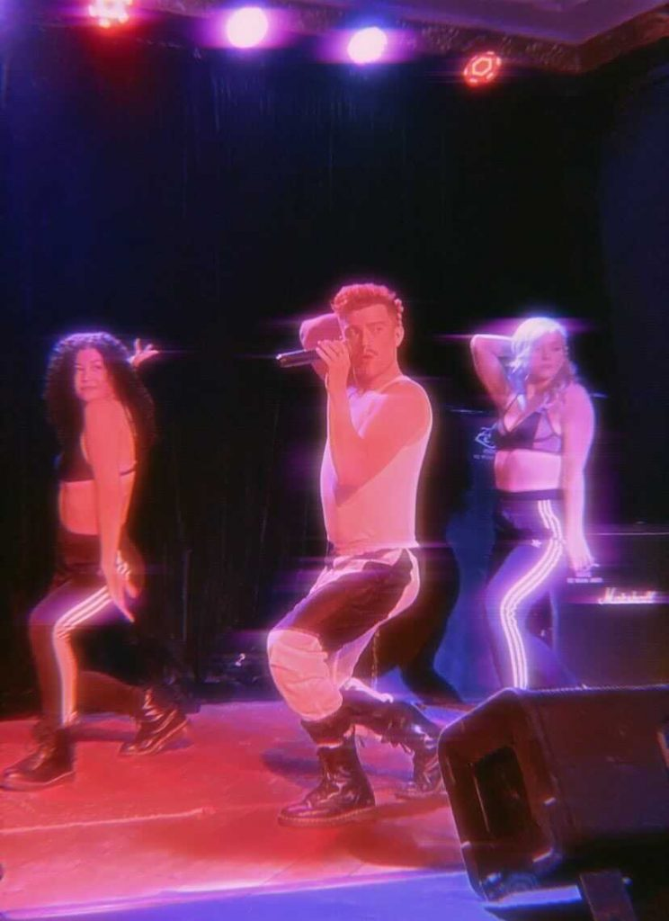 Jasey Fox perfoming with two backup dancers, the image has a VCR glitchy effect