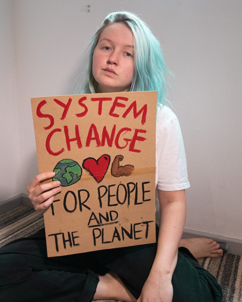 Photo of Izzy sat on the floor with a cardboard sign. They have aqua long hair, wear a white t-shirt and black jeans. The hand painted sign reads: 'System change for people and the planet'.