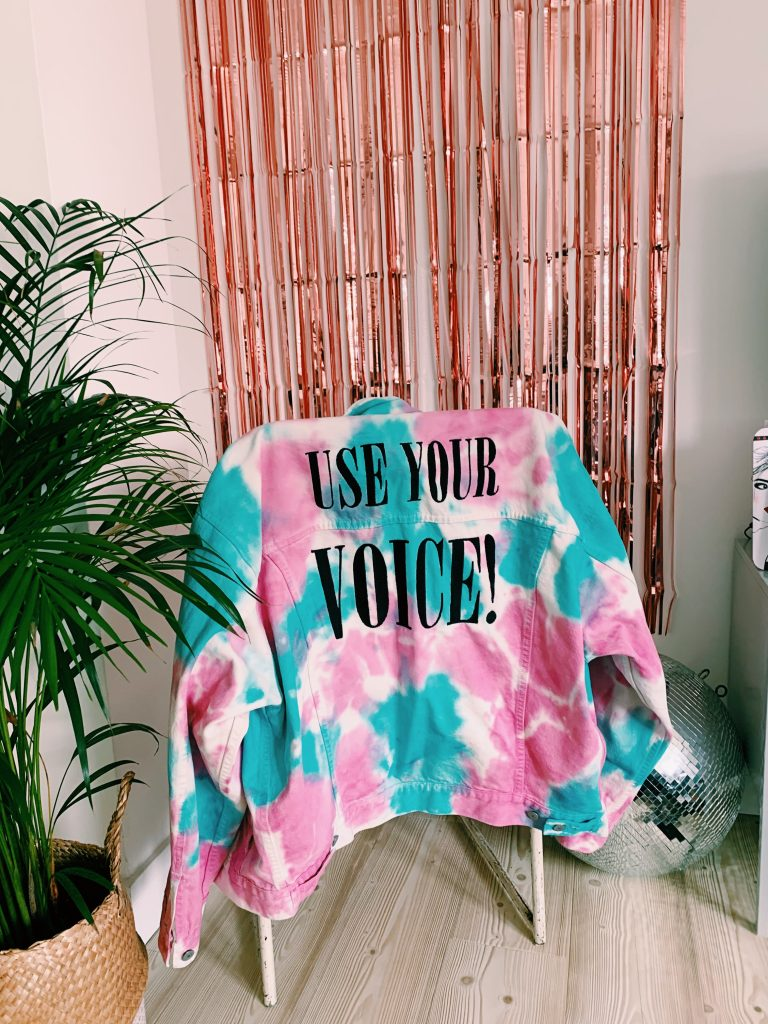 Coloured photo of Levis pink, blue and white tie dye denim jacket with the words 'USE YOUR VOICE' stitched on the back. The jacket hangs on the back of a chair. A plant is in the left hand corner. A large silver disco ball in the back right corner and a rose gold tinsel curtain hangs off the white wall in the background.