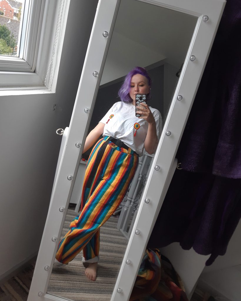 Mirror selfie of Izzy. They are wearing rainbow striped trousers and a white t-shirt with rainbow tassels. They have purple hair and are standing in front of a long white mirror in their bedroom.