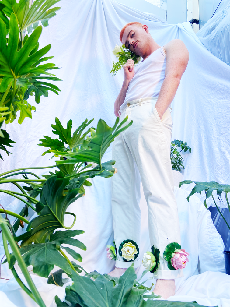 Jasey Fox, a causasian man with bright ginger hair and a moustache, stands amongst house plants in a room with white fabric walls. He is wearing a white tank top and white trousers, flowers are stitched into his trousers at the ankle