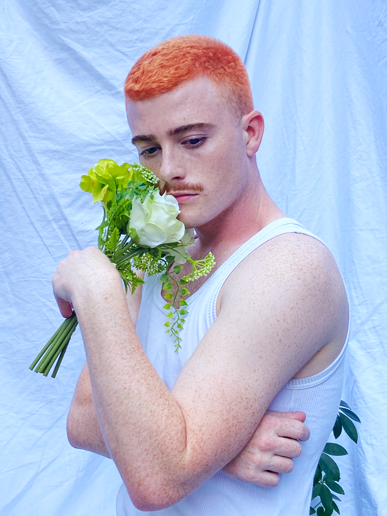 Jasey Fox, a causasian man with bright ginger hair and a moustache, stands holding a bunch of green flowers to his face. He is looking with a glazed expression at the floor, away from the flowers, as if thinking.
