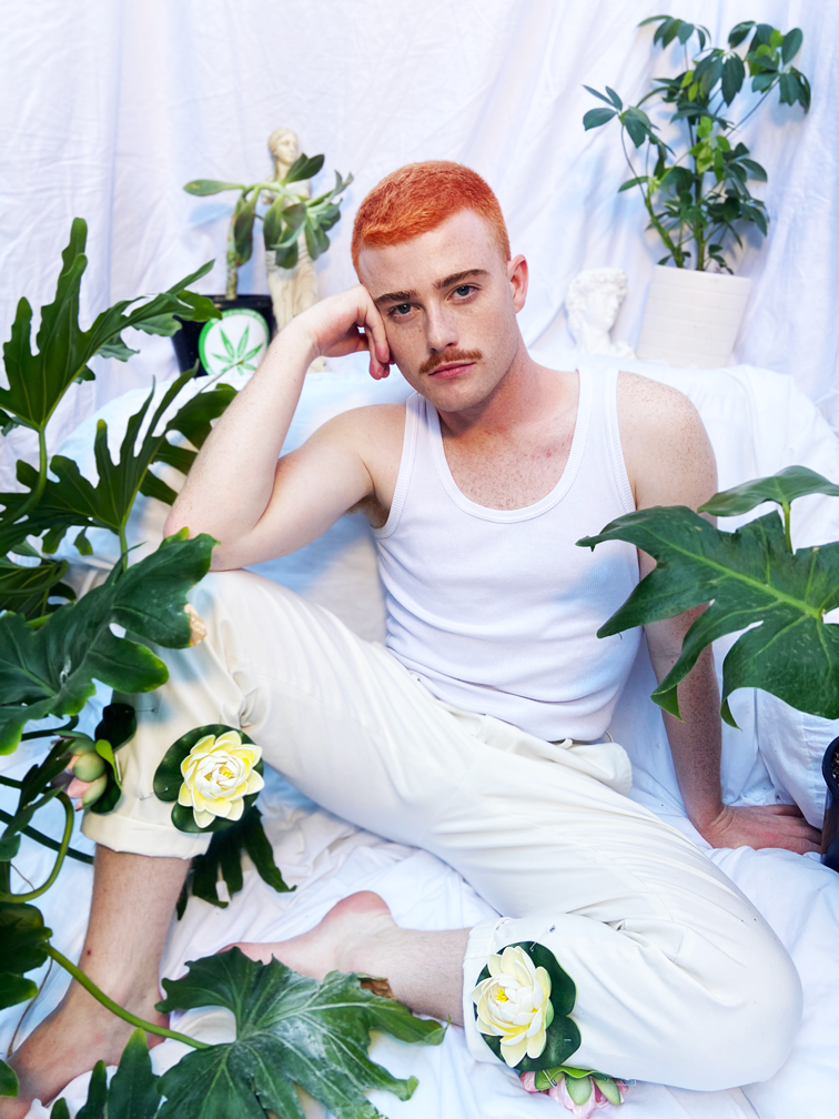 Jasey Fox, a causasian man with bright ginger hair and a moustache, sits amongs house plants in a room with white fabric walls. He is wearing a white tank top and white trousers