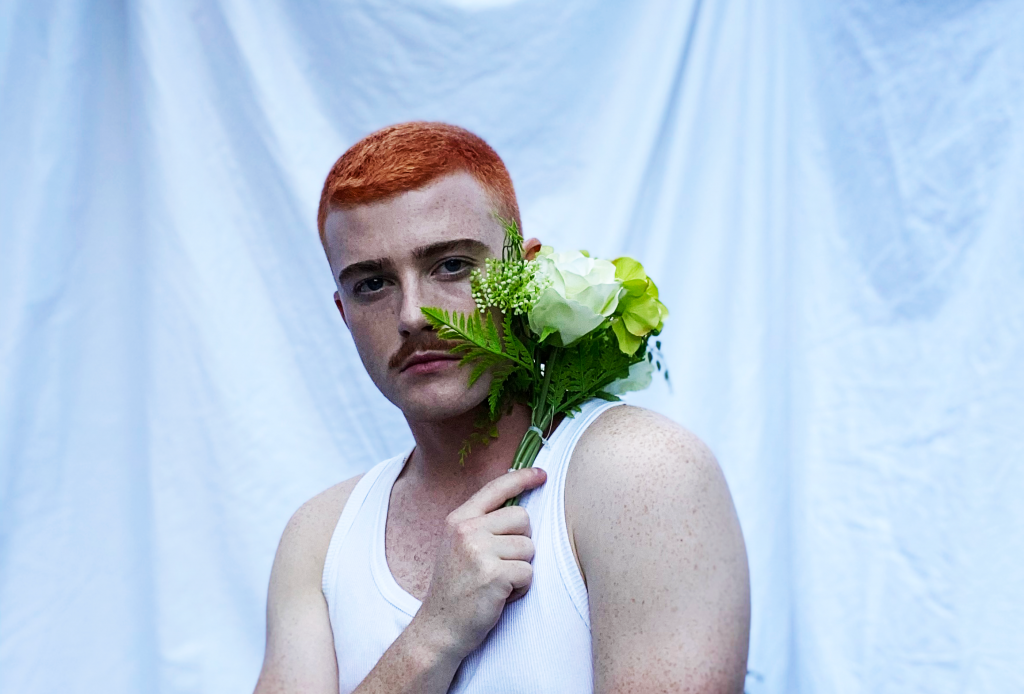 Jasey Fox, a causasian man with bright ginger hair and a moustache, stands holding a bunch of green flowers to his face. He is looking with directly at the camers