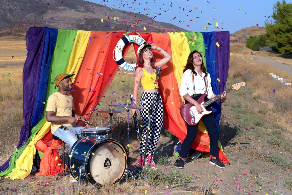 Lucy and her band perform outside in front of a rainbow flag.
