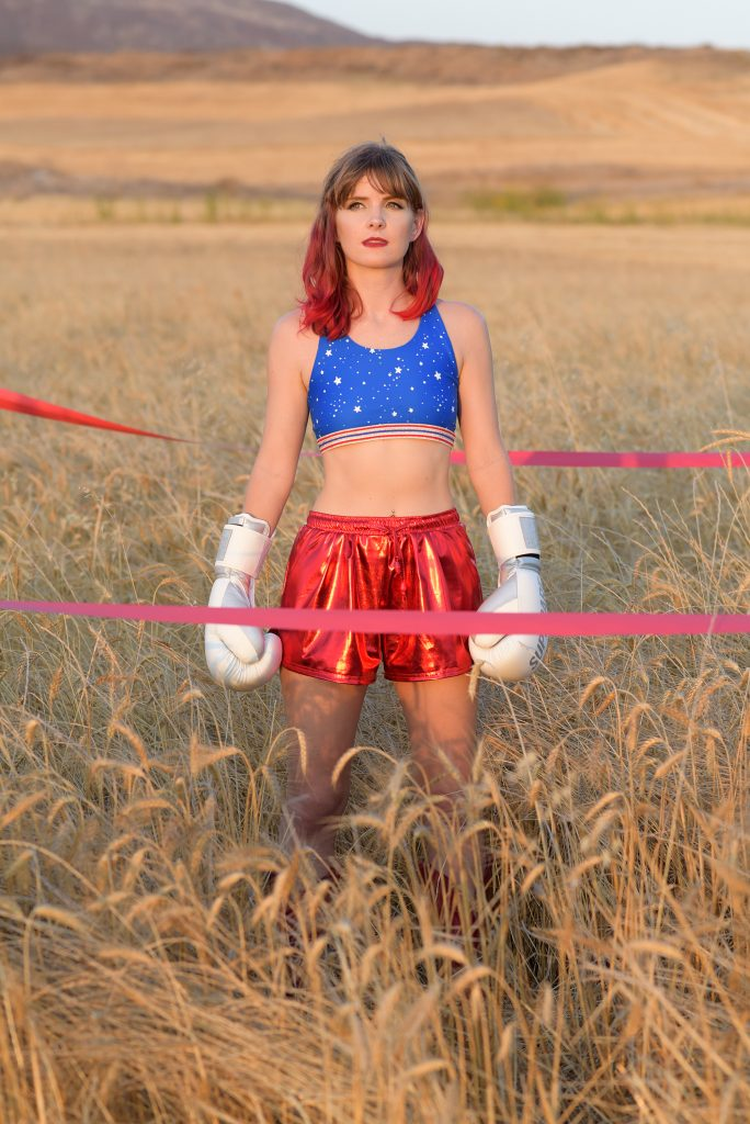 Lucy stands in a field, dressed as a boxer in red, white and blue.