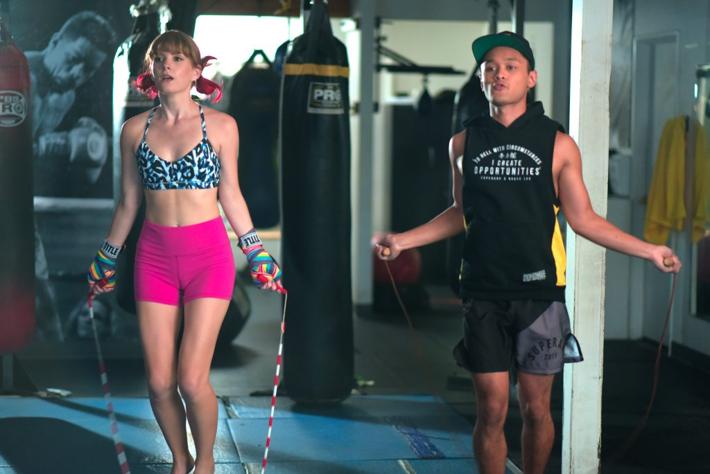 Lucy trains alongside an instructor in the gym featured in the video.