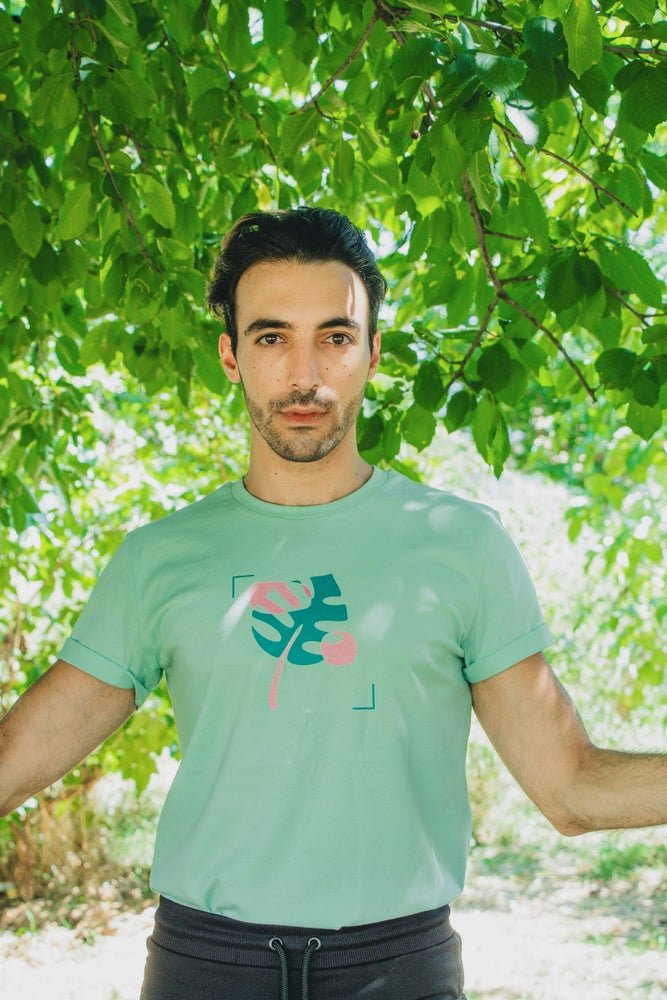 Femme Forte model with short, dark beard and slick back dark hair wears mint green with dark green and pink plant graphic on the front. The tee is 100% organic cotton and gender neutral.