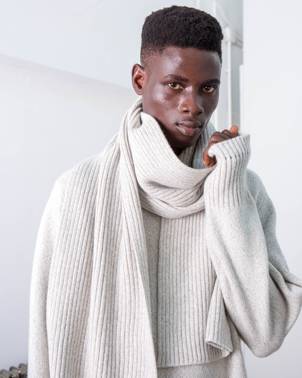 Black Riley Studio model with short afro hair dressed in light grey recycled cashmere scarf and light grey recycled cashmere sweater