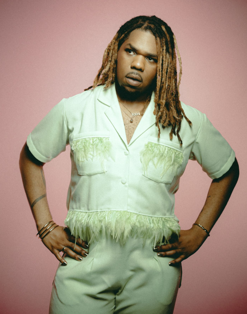 MNEK stands with thin bangles on his arms and his hands on his hips, looking off to the side in equal parts inquisitive and fierce. He is wearing a mint green fringed body suit against a salmon pink background, his locks stylishly fading from black roots to bleached tips as they rest on his collar bone.
