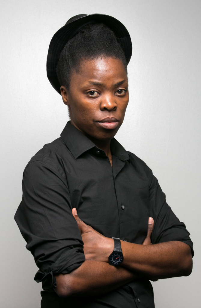 Zanele looks directly into the camera with an unwavering stare, hair swept up under a black fedora. They are crossing their arms in front of their body, tucked under their armpits, wearing a chunky black sports watch and black shirt with the sleeves rolled up.