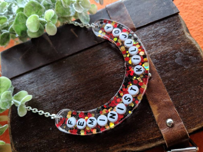 On a dark wood background with leaves to the top of the picture, a crescent-shaped resin pendant is filled with red, yellow and black glitter, and the words 'Feminist Killjoy' in small round white letter tiles.