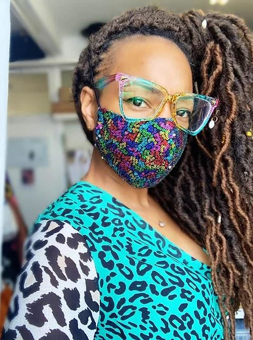 Velvet is now wearing a green and white bold leopard print outfit, her hair tied to the side, rainbow-framed glasses and a bright rainbow sequinned mask