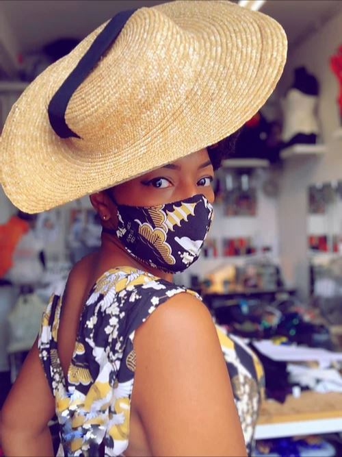 Velvet is wearing a large floppy straw hat, looking over her shoulder at the camera. She is wearing a beautiful black dress with white and yellow dotted floral patterns, and a mask to match