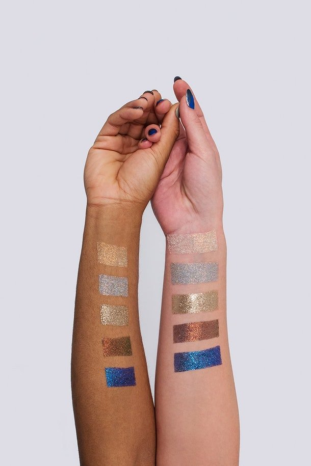 Two arms side by side, one of a lighter skin tone and one of a darker skin tone, are holding hands while stretched out. On their arms are shimmering colour swatches of pale peach, silver, gold, bronze and a rich metallic blue.