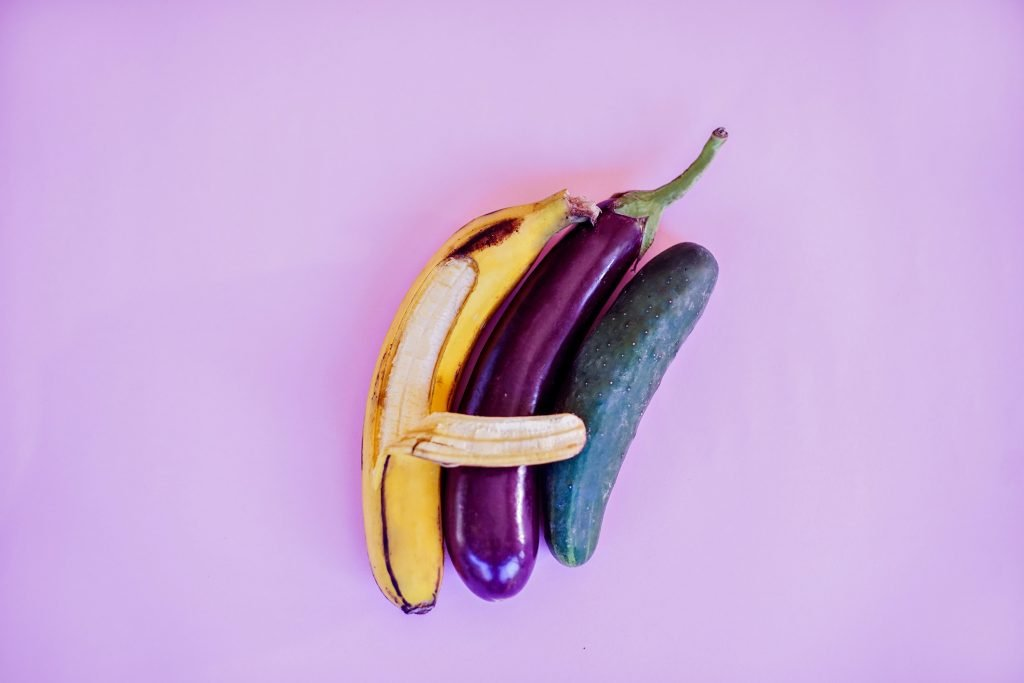 A banana, an aubergine and a courgette lie together in post-coital bliss.