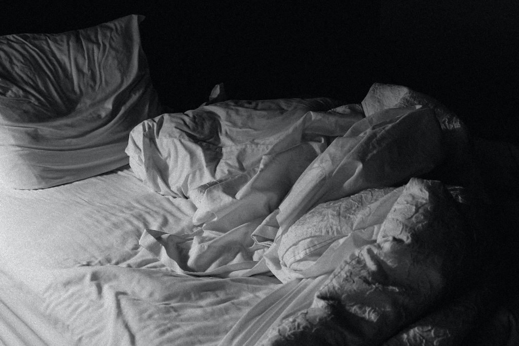 A bed that has been slept in, the sheets are white and the image is black and white. Pillow stacked at the end of the bed as if someone has been sitting in it for a while.
