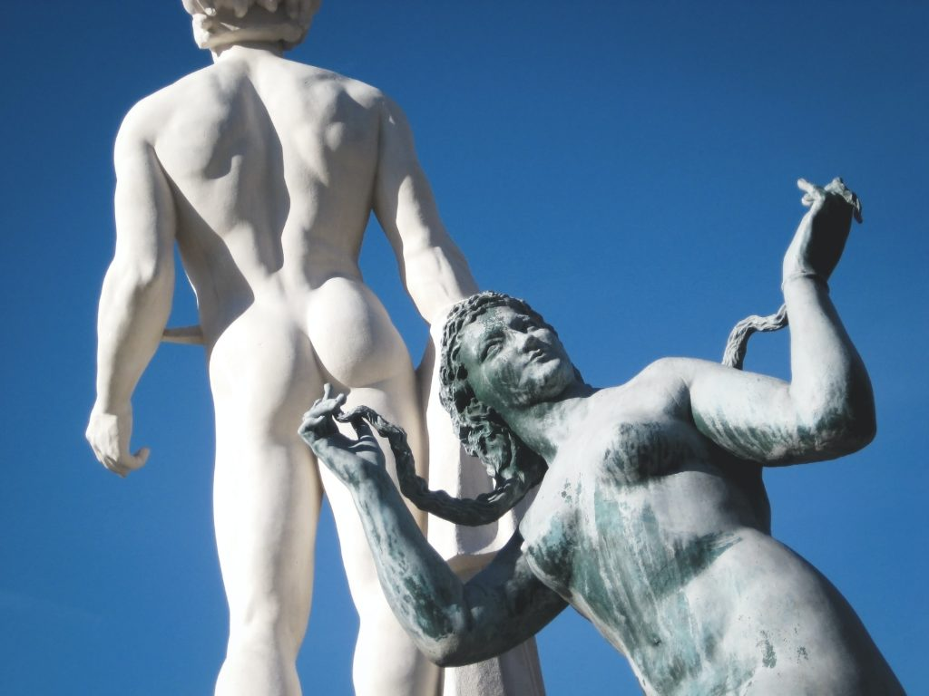 A marble statue of a women is positioned so it appears her finger is penetrating a male statue's anus.