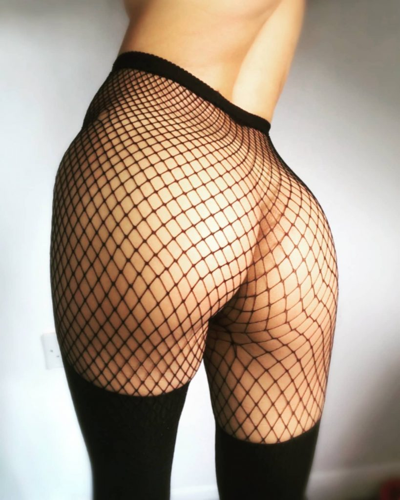 In netting stockings, a zoomed-in shot of smooth naked buttocks turned to the camera, with a clearly naked torso cropped just under the breast line.