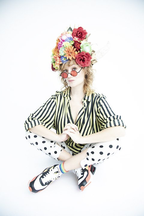 Colour photograph of Dolche. She's in a stark white setting. She wears white, black, orange and yellow Nike trainers. White trousers with black spots. A yellow and black striped shirt that isn't buttoned all the way to the collar. She has black framed round sunglasses with orange lenses. On her head she's wearing a multi-coloured floral crown with white bull horns on either side. She's sat on the floor, with her legs crossed and knees slightly raised. Her elbows are resting on each knee and the hands are interlocked together in the middle. She has her sunglasses on the end of her nose and is looking towards the camera with a slightly serious expression.