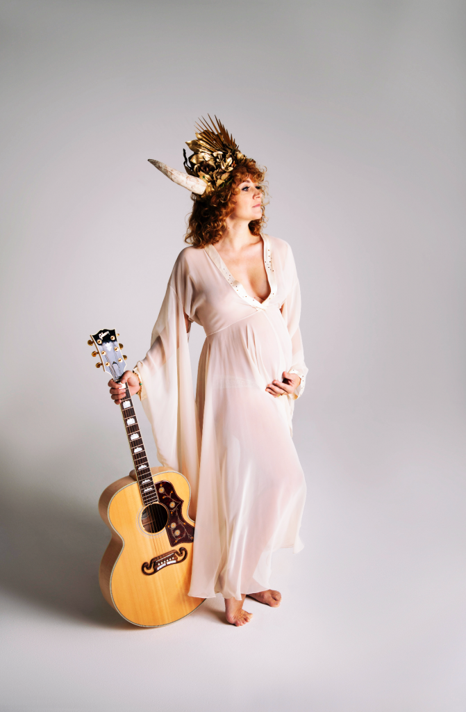 Vertical coloured photo of Dolche. She is wearing a golden crown with two white horns sticking up on either side. She has dark, blonde/ginger curly hair which is worn down. She has a short fringe which sits above her eyebrows. She is wearing a cream sheer long kimono style dress with batwing draping sleeves. She is stood up facing to the right. In her right hand, on the left hand side of the photo, she is holding a wooden acoustic guitar. Her left hand, on the right hand side of the image is holding her belly / bump. She is stood with her right leg slightly bent. She is barefoot.