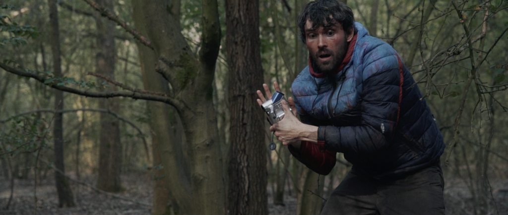 Arron Blake as Norman holding a video camera in an image from the film. He is wearing the tired blue and red coat from the previous images. He is in motion, perhaps moving from a crouching position, his face concentrating and looking downwards. The background is dense green woods.