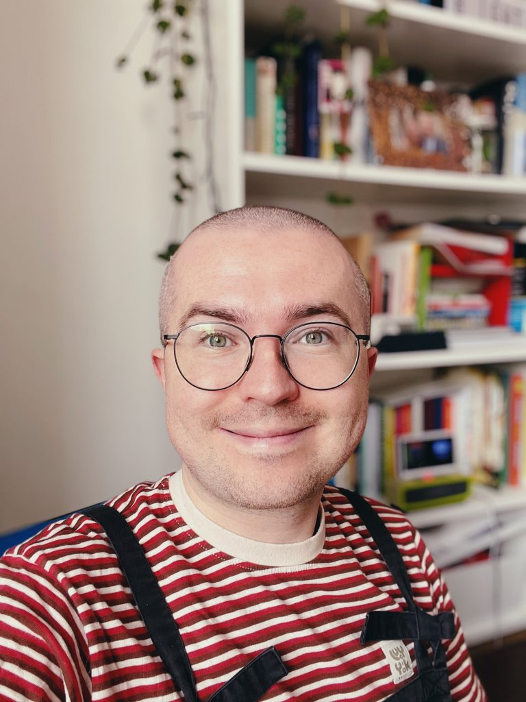 Cropped colour portrait photograph of Tom. They have a shaved head, round glasses and a closed lip smile expression. They are wearing a striped red and white top and black dungarees. Behind them is a bookcase with books and a plant hanging down.