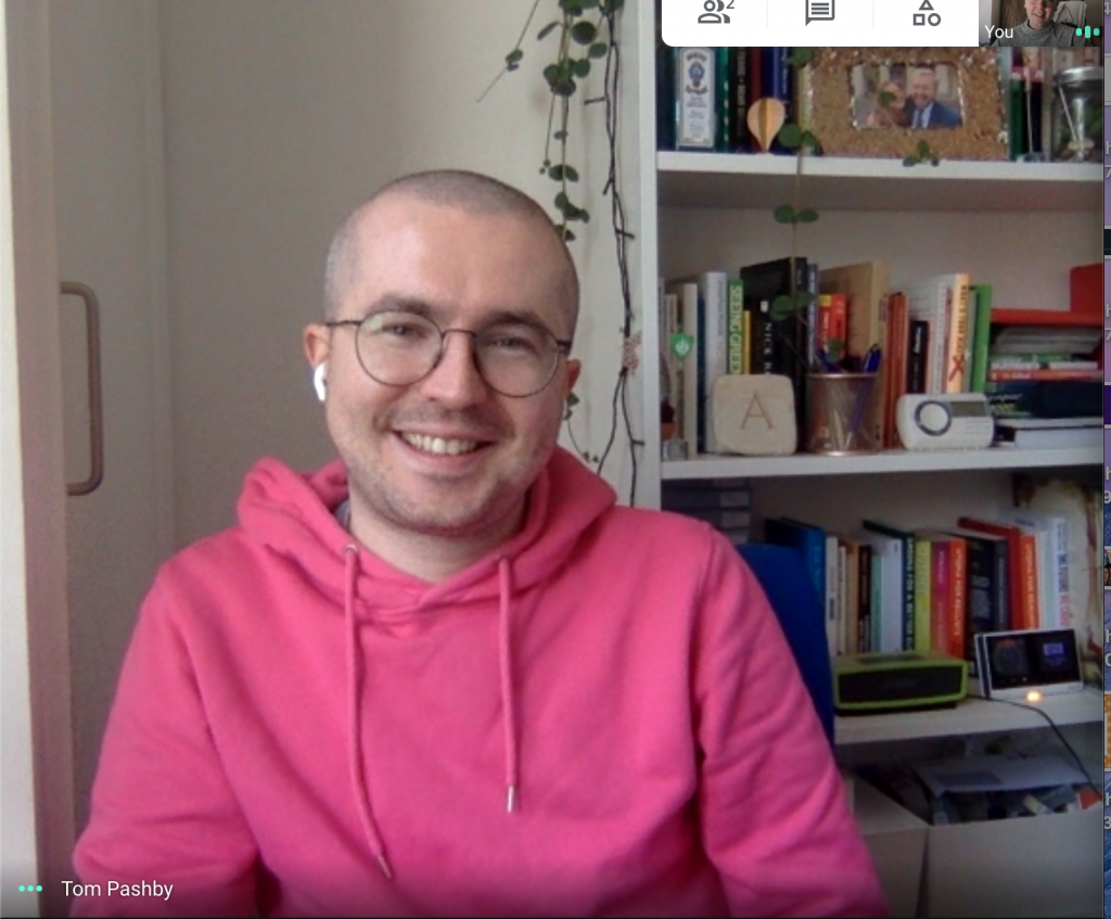 Screenshot of Tom and Lucy's googlehangout interview. Tom is wearing a bright pink hooded jumper, earphones, round glasses and is smiling with an open mouth. Behind them is a bookcase with books, photos, a speaker and a plant hanging down.