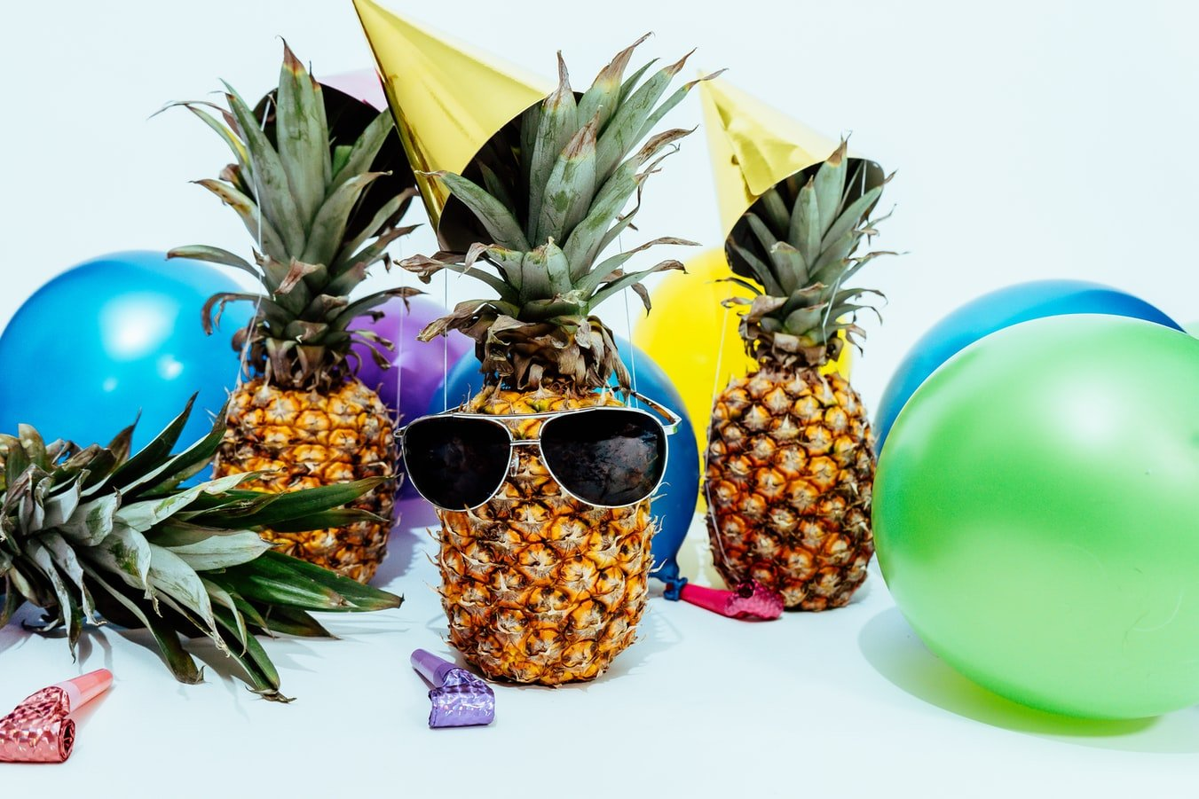 hree pineapples are at a party, surrounded by balloons with party hats on. The middle pineapple is rocking a pair of super cool sunglasses.