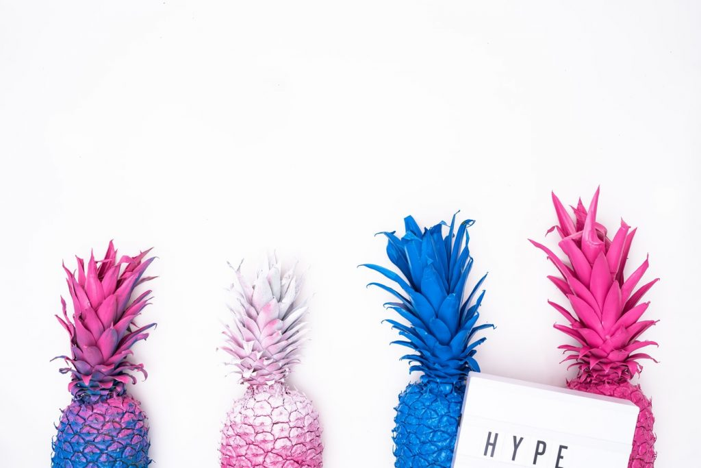 On a white background, lined up are the tops of four pineapples, spray-painted purple, white, blue and pink. In front of the right hand one is a page with the word 'hype' in all capitals.