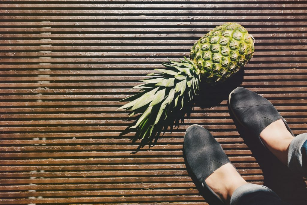 On wooden slatted decking, a pineapple is flopped sadly on the floor at someone's feet, wearing slightly battered old loafers.