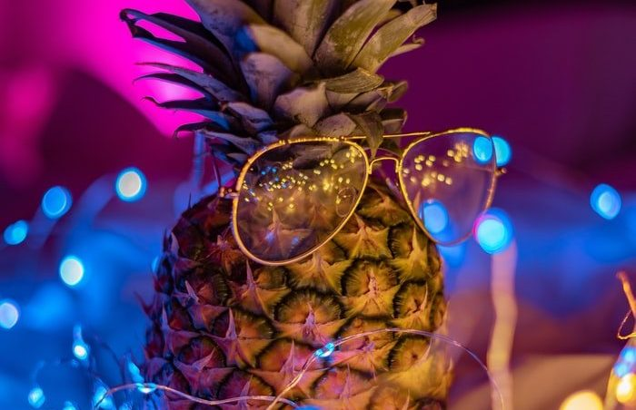 In super funky bisexual lighting, a cool, astute looking pineapple rocks its sunglasses, surrounded by a string of tiny little glowing fairy lights