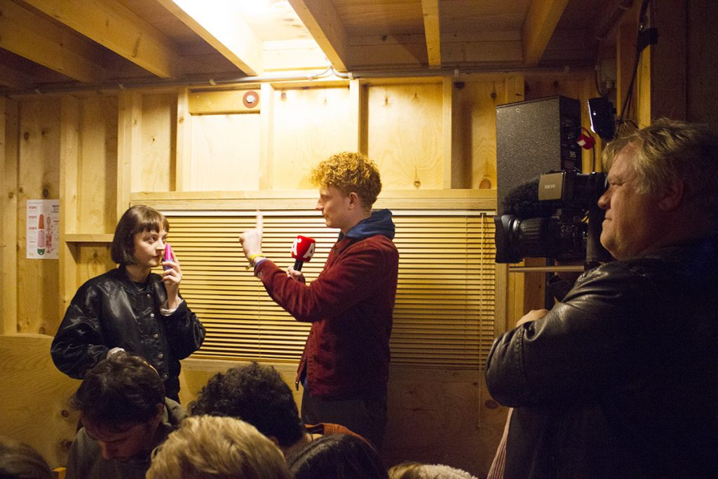 Photograph of Alice holding a designed sexy toy. She is speaking to an interviewer and they are holding a finger to resemble the shape of the toy. A cameraman is to the left of the member and is filming the chat. They are in a wooden plied room with posters of sex toy parts and instructions to step up on the wall