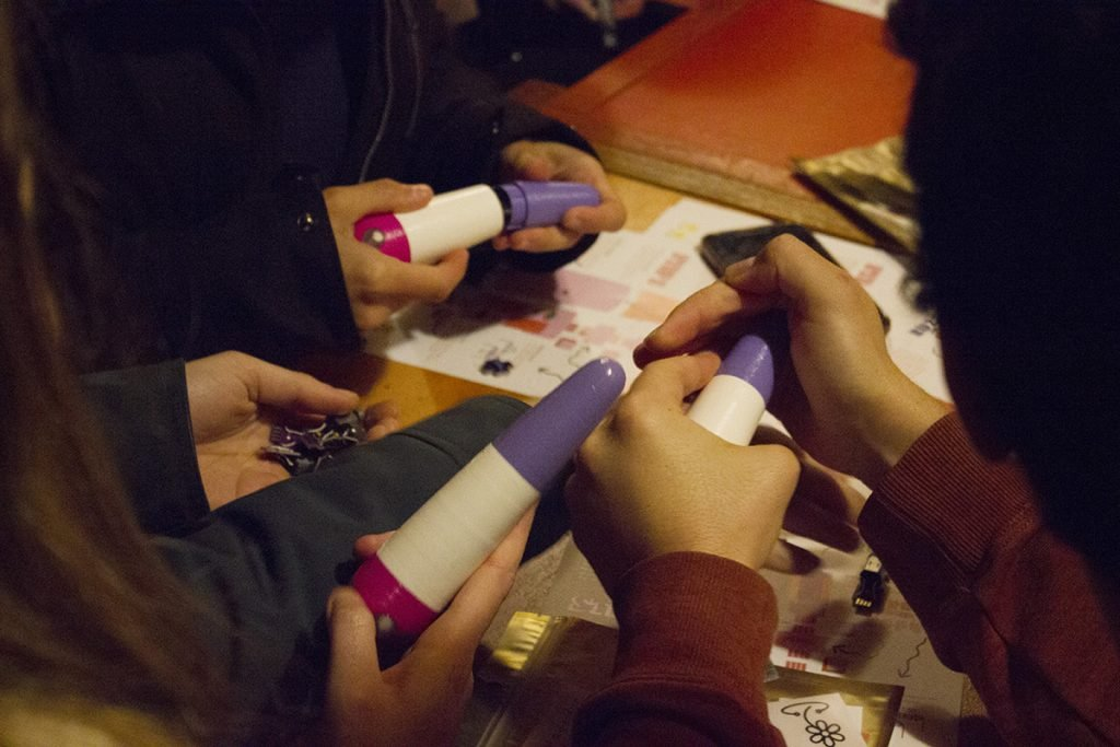 Photograph of workshop candidates hands. Making toys in the final stage by pushing together the two pieces of coverage that shape the toy. The toy is shaped small and long and is curved at the top. It is a purple and white toy with an adjuster setting of pink at the bottom.