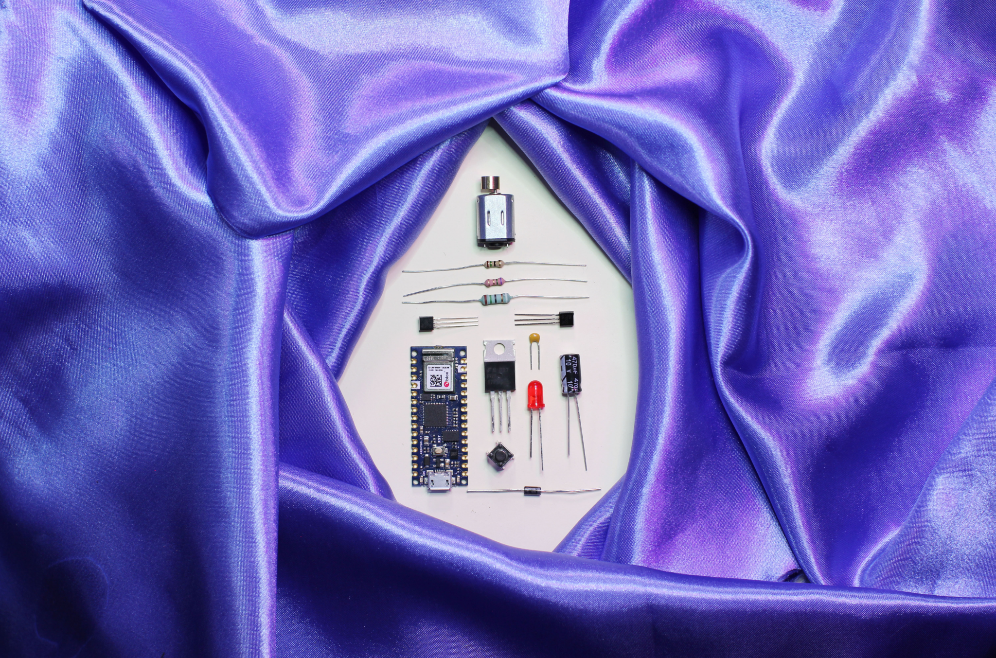 Photograph of sex toy parts on a purple velvet sheet background. The parts are placed in a hole cut in the middle shaped like a vulva or triangle shape.