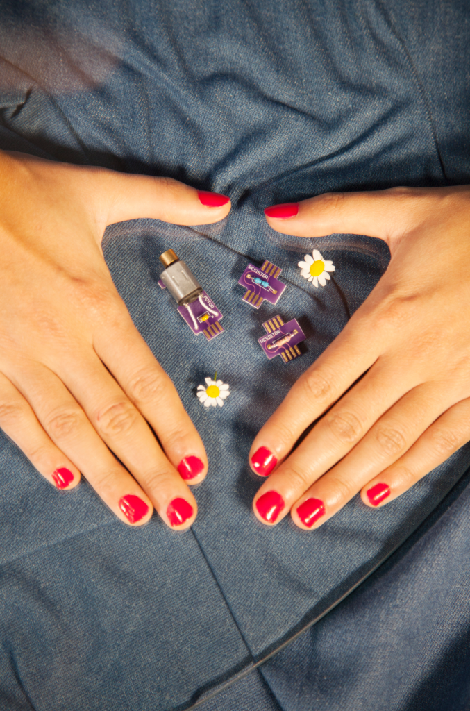 Photograph of sex toy parts on a jean textured background with daisies around them. There are pairs of a person's hands with red nail varnish shaped like a triangle or surrounding the parts. The second image is of the same pair of hands holding the parts presenting it to the camera with daisies. The background is denim fabric.