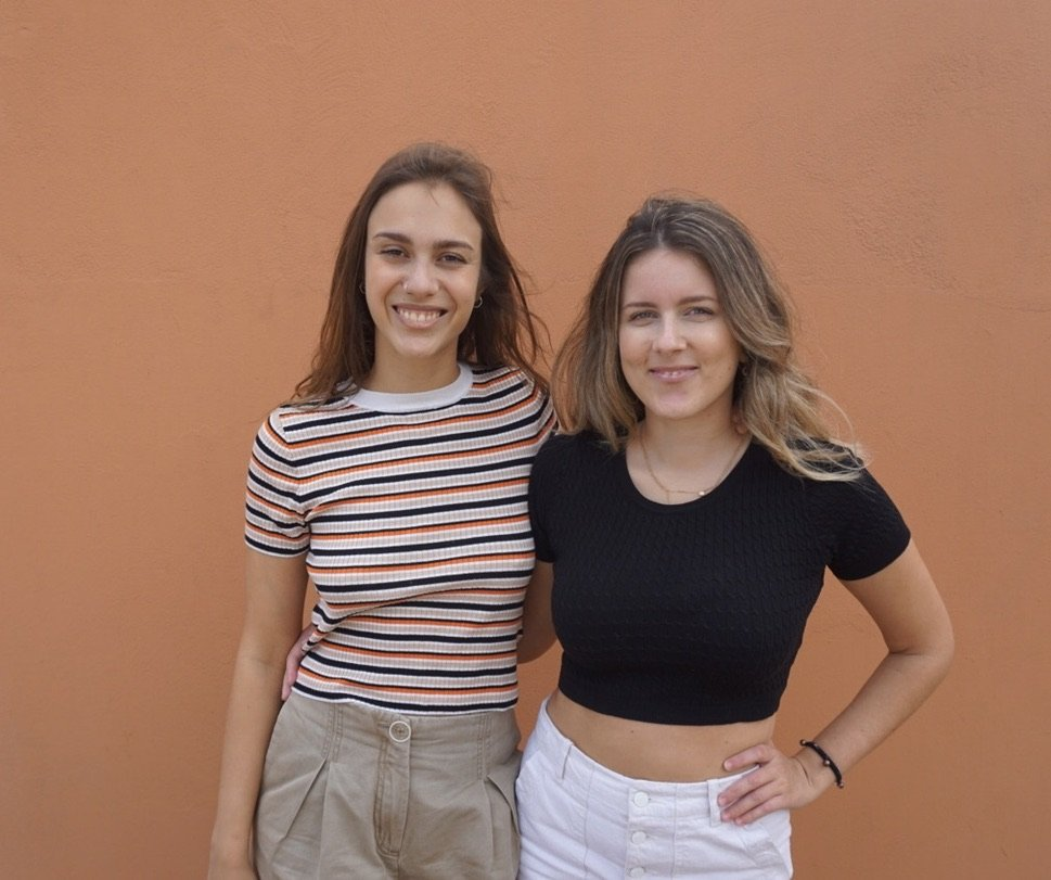 Colour portrait photograph of Vibio's co-founders. Alma stands on the left with her arm around the back of Patricia. She is wearing a cream, orange and black striped t-shirt with pale cream trousers. They have long brown hair and are smiling with their teeth showing. Patricia is on the right. She has blonde brown long curled hair and is wearing a black cropped t-shirt with white trousers. She is smiling, showing a little teeth and has one hand on her hip and the other around Alma. The background is a plain painted terracotta coloured wall.